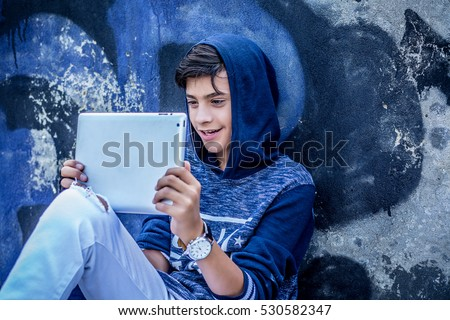 Happy smiling teenager looking in his pad reading news watching movies isolated outdoors graffiti background wall. Positive emotions face expression