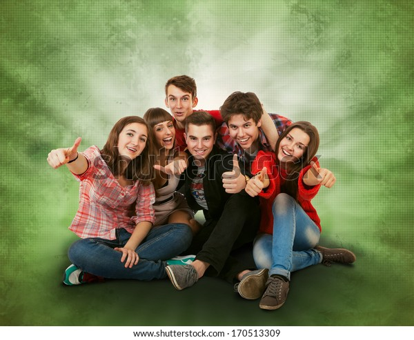 Happy smiling teenagers group on bright green background