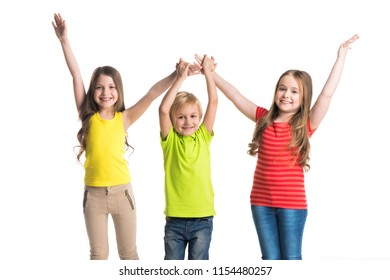 Happy smiling three children in colorful clothes holding raised hands isolated on white background