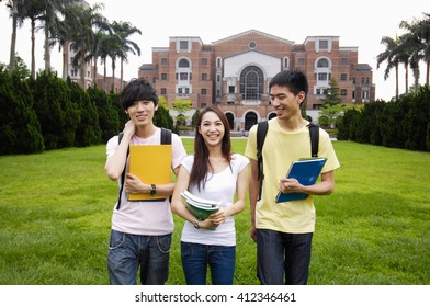 Happy smiling three  standing together with books at a campus