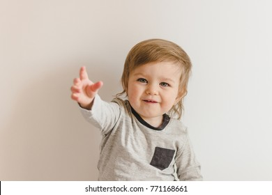 Happy smiling toddler girl stretching her arm