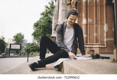 Happy and smiling tourist is sitting on the church's steps on the street. He took a cup of coffee and decided to have some rest. Now he is studing the map of the city. His camera is placed near the