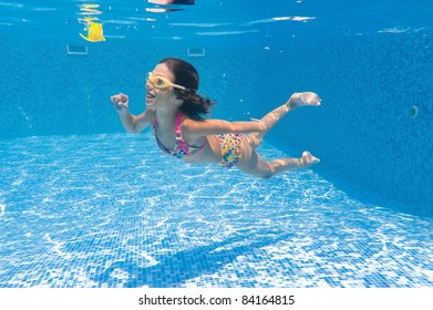 Happy smiling underwater kid playing in swimming pool. Active girl swims and having fun. Child sport on summer vacation
