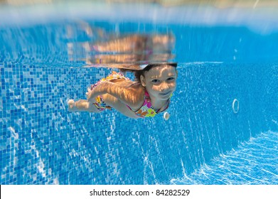 Happy smiling underwater kid in swimming pool. Active girl swims and having fun. Child sport on summer vacation