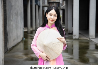 Happy smiling Vietnamese girl; portrait of exotic asian Vietnam woman in traditional Vietnamese Ao Dai dress