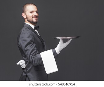 Happy smiling waiter in black suit holding a silver tray over dark background