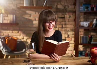 Happy smiling white woman reading book at home in the living room. wearing red glasses, drinking wine. Warm colors.