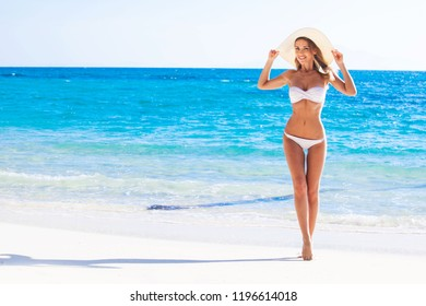 Happy smiling woman in bikini and sunhat on sea beach