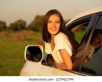 Happy smiling woman in the car looking out of window. Beautiful caucasian girl in the car on the nature.