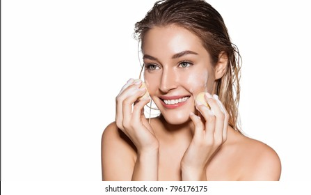 Happy smiling woman cleaning face skin with sponge and foam. Natural cosmetic concept. Facial beauty treatment concept. Studio portrait isolated on white.