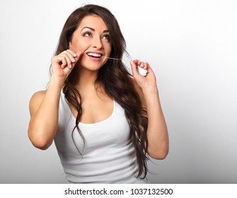 Happy smiling woman cleaning the teeth the dental floss on white background with empty space. Dental Hygiene.