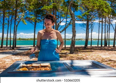 Happy smiling woman cooking barbeque on the beach in Australia