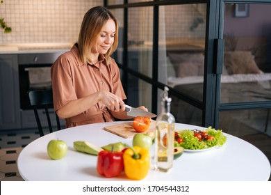 Happy smiling woman cutting fresh organic tomato with a knife for vegetable salad in modern kitchen. Smiling slim vegetarian female prepare healthy vegan dinner meal. Concept of healthy eating.