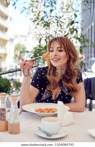 Happy smiling woman in dotted dress eating pasta. Pretty female enjoying lunch at summer terrace.