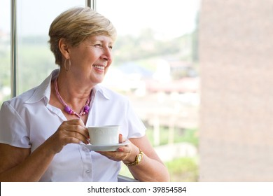 happy smiling woman drinking coffee by the window