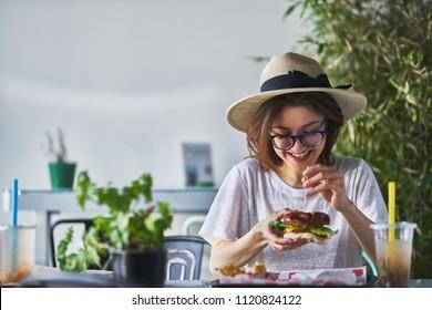 happy smiling woman eating healthy vegan burger at trendy restaurant