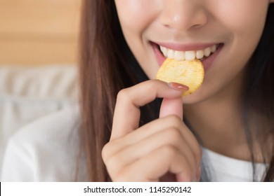 happy, smiling woman eating potato chips or crispy fried potato; unhealthy food or fried food concept; young adult asian persian woman or asian middle east model