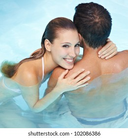 Happy smiling woman embracing attractive man in blue water