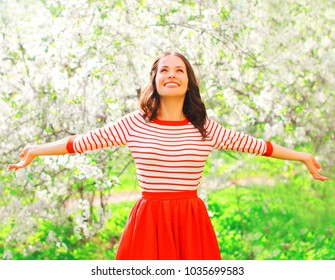Happy  smiling woman enjoying smell flowers over spring garden background