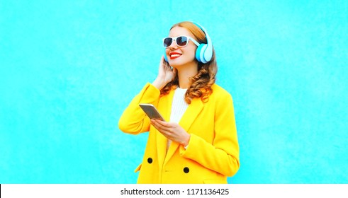 happy smiling woman enjoys listens to music in headphones holds smartphone on colorful blue background