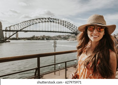 Happy smiling woman exploring Sydney, with Harbour Bridge in the background.