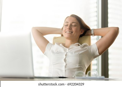Happy smiling woman feels relaxed in office home, enjoying moment, no stress at work, practicing breathing at workplace, taking pleasure in meditating sitting with eyes closed, portrait head shot
