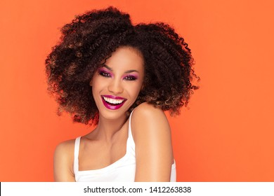 Happy smiling woman with glamour makeup. Photo of young african woman on orange background.