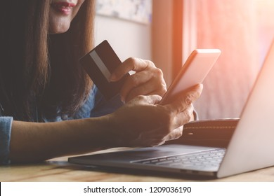 Happy smiling woman hand holding credit card and  using mobile smart phone for online payment and shopping, mobile banking , e commerce concept.