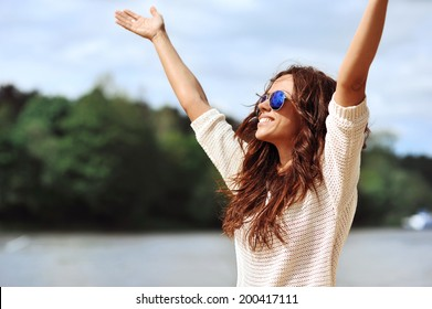 Happy smiling woman with hands raised - outdoor portrait