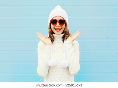 Happy smiling woman having fun wearing a heart shape sunglasses, knitted hat, sweater over blue background