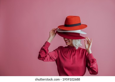Happy smiling woman hides her face under many hapy. Funny posing model. Fashion, shopping, sale, discount, advertising conception. Copy, empty space for text