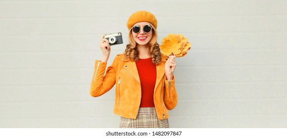 Happy smiling woman holding autumn yellow maple leaves, retro camera taking picture in french beret over gray wall background