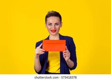 Happy smiling woman holding red envelope – isolated yellow background wall. studio shot horizontal image. Portrait with copy space