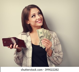 Happy smiling woman holding wallet and dollars and thinking how to spent its. Toned portrait