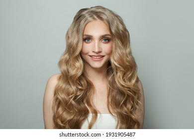 Happy smiling woman with long curly hairstyle on white background