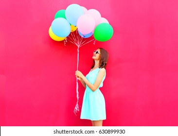 Happy smiling woman is looking on an air colorful balloons having fun over a pink background