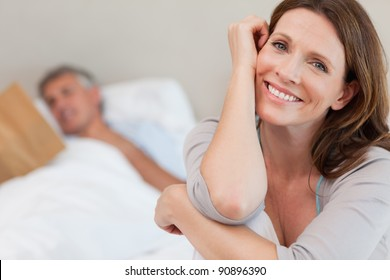 Happy smiling woman on the bed with husband reading behind her