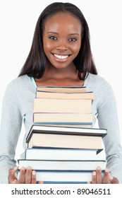 Happy smiling woman with pile of books against a white background
