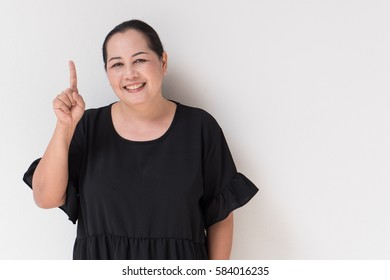 happy, smiling woman pointing up one finger, middle age model. Concept of success, acceptance, winning, showing or presenting something