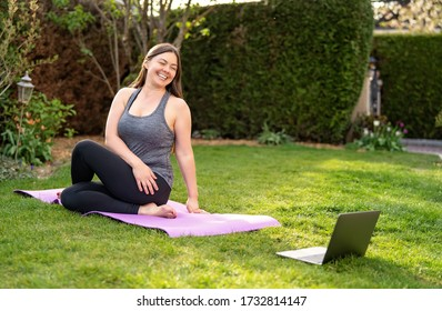Happy smiling woman practicing pilates lesson online in garden doing stretching  outdoors during quarantine. Doing sport at home following guide or online tutorial or trainer instructions.