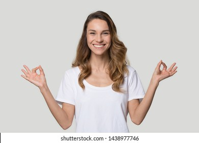 Happy smiling woman practicing yoga exercise, meditating, breathing, stress relief concept, calm peaceful healthy young female looking at camera, showing mudra gesture, isolated on studio background