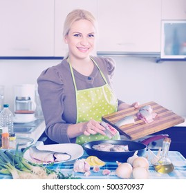Happy smiling woman putting pieces of fish in frying pan at home kitchen