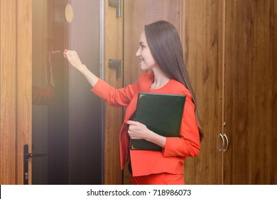 Happy smiling woman in a red suit with documents in hand knocking at the door to the boss. A business meeting, a successful business. Business people concept.