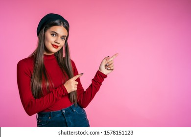 Happy smiling woman in red wear presenting and showing something isolated on pink background. Portrait of girl, she pointing with arms on her left with copy space.