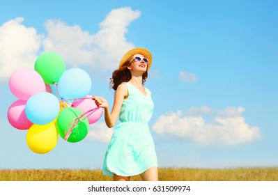 Happy smiling woman runs with an air colorful balloons is enjoying a summer day on a meadow blue sky
