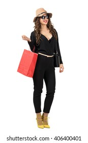 Happy smiling woman shopper holding red paper bag looking away. Full body length portrait isolated over white studio background.