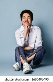 Happy smiling woman with short brunette hair in stylish blue jeans with zippers and white shirt is sitting cross legged on the floor holding her hand at her chin