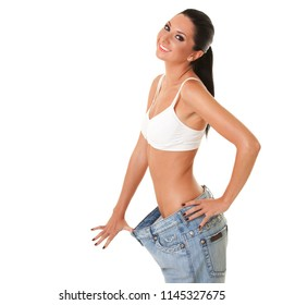 Happy smiling woman shows her weight loss by wearing an old jeans, isolated on white background. Healthy lifestyle, dieting, fitness, weight loss concept. Tanned woman looking into the camera