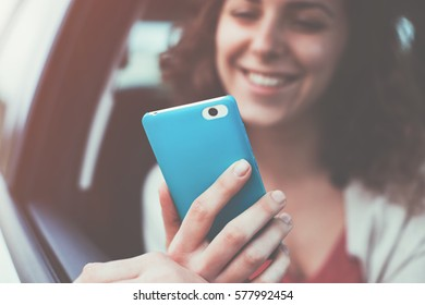 Happy smiling woman sitting in the car and looking at her mobile phone