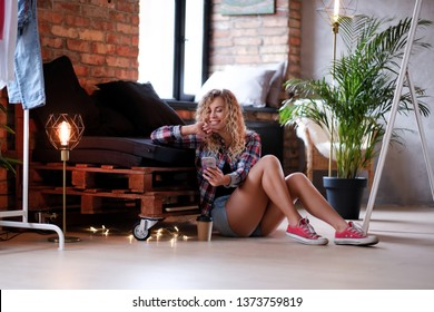 Happy smiling woman is sitting next to the pallet sofa and holding her smartphone. She wear hotpants and checkered shirt. Modern loft with brick wall at background.